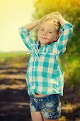 Funny little girl in the countryside. Happy childhood. Western style, jeans.