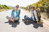 Attractive couple sitting on the road hitch hiking on a sunny day