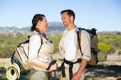 Hiking couple smiling at each other in the countryside on a sunny day