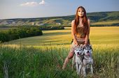 Girl with dogs  in a wheat field at sunset