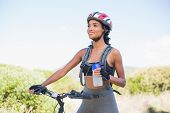 Fit woman going for bike ride holding water bottle on a sunny day in the countryside