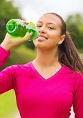 fitness, park, drink and sport concept - smiling african american woman drinking from bottle outdoor