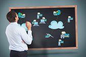 Thinking businessman holding pen against cloud computing doodle on blackboard