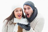 Attractive young couple in warm clothes blowing on white background
