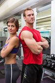 Fit attractive couple smiling at camera with arms crossed at the gym