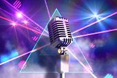 Retro chrome microphone against digitally generated laser lights background