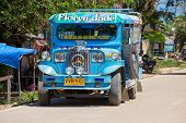Jeepneys Passing, Philippines Inexpensive Bus Service.