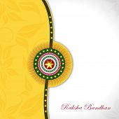 Beautiful rakhi on floral decorated yellow and grey background for Happy Raksha Bandhan celebrations