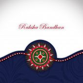 Beautiful Rakhi on grey and blue background on the occasion of Raksha Bandhan festival.