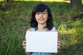Lovely teen-girl holding clean white sheet paper, in the park (banner for your message)