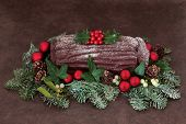 Chocolate yuletide log with red bauble decorations, holly, ivy, mistletoe, snow covered fir and pine cones over brown handmade lokta paper background.