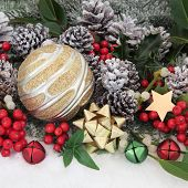 Christmas bauble decorations, holly and winter greenery over snow background.