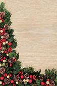 Christmas background border decoration with red baubles, holly, ivy, fir leaf sprigs and pine cones over oak.