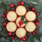 Christmas mince pie cakes and red baubles with holly and fir.