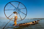 Myanmar travel attraction landmark - Traditional Burmese fisherman with fishing net at Inle lake in