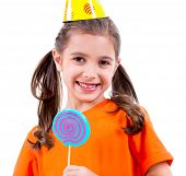 Portrait of little cute girl in orange t-shirt and party hat with colored candy - isolated on white.