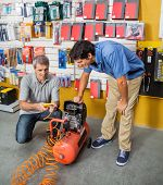 Father and son examining air compressor in hardware store