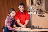 Portrait of happy young male carpenter measuring wood with female coworker in workshop