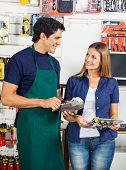 Happy woman with screwdriver set looking at worker swiping credit card in hardware store