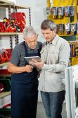 Senior salesman with customer using digital tablet in hardware store