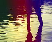 Female Legs In Rolled Jeans In Sea Water.
