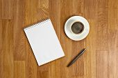 Blank Notepad With Office Supplies And Cup Of Coffee On Wooden Table.