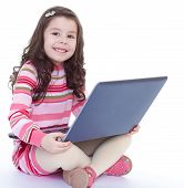 little girl holding a laptop on his knees