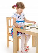 pic of diligent  - beautiful little girl reading a book diligently sitting at the table - JPG