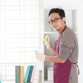 Asian man housekeeping. House husband doing house chores, with home interiors.