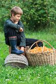 Boy looking at wicker basket full of chanterelles