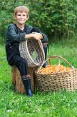Smiling boy sitting near basket of chanterelles