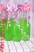 Bottles of drink with straw on table on decorative background