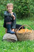 Happy boy sitting near basket full of chanterelles
