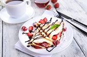 Delicious pancakes with berries on table close-up