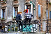 VENICE, ITALY - NOVEMBER 13, 2013: Gondoliers in traditional dress sitting on the bridge. Gondolier must be Venetian by birth, it is one of the oldest professions in the world controlled by a Guild.