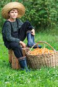 Boy in straw hat sits with basket of chanterelles