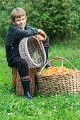 Boy and basket full of chanterelle mushrooms