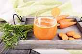 Glass of carrot juice and fresh carrots on wooden tray on table close up