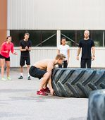 Group of athletes motivating friend in flipping tire outdoors