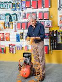 Full length of senior man examining air compressor in hardware store