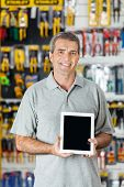 Portrait of confident mature man displaying digital tablet in hardware store