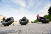 Group of young athletes doing tire-flip exercise outdoors