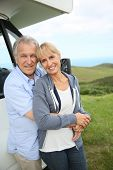 picture of motorhome  - Senior couple standing by motorhome in countryside - JPG
