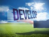 Businesswomans hand presenting the word develop against sunny green landscape