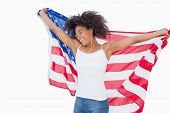 Pretty girl wrapped in american flag cheering on white background