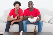 Football fans in red sitting on couch with beer and popcorn at home in the living room