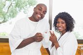 Happy couple having coffee together in bathrobes at home in the kitchen