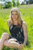 Pretty blonde in sundress sitting on grass on a sunny day in the countryside