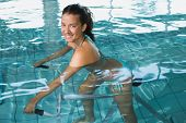 foto of day care center  - Fit brunette using underwater exercise bike in swimming pool at the leisure centre - JPG
