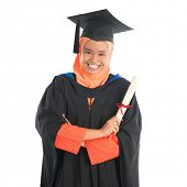 Portrait of smiling Asian female Muslim student in graduate gown showing graduation diploma standing isolated on white background.
